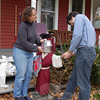 "Jessica Buster and David Turkington have amused themselves and passersby of their Sandy Hook home for the past year by dressing up an antique lawn jockey named Charlie, near the front steps of the house. Here, Ms Buster and Mr Turkington pose with ""Crusader Knight Charlie.""  (Crevier photo)"