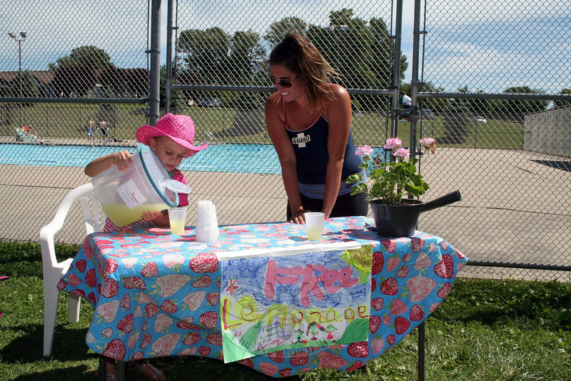 Kylie Kuroglian carefully pours lemonade for Alissa Keyes, a lifeguard and swim instructor at Tashua Pool in Trumbull. Kylie was hosting her third Newtown Kindness lemonade stand of the summer on Monday, giving away cups of lemonade and encouraging others to do something nice for someone else in return. (Hicks photo)