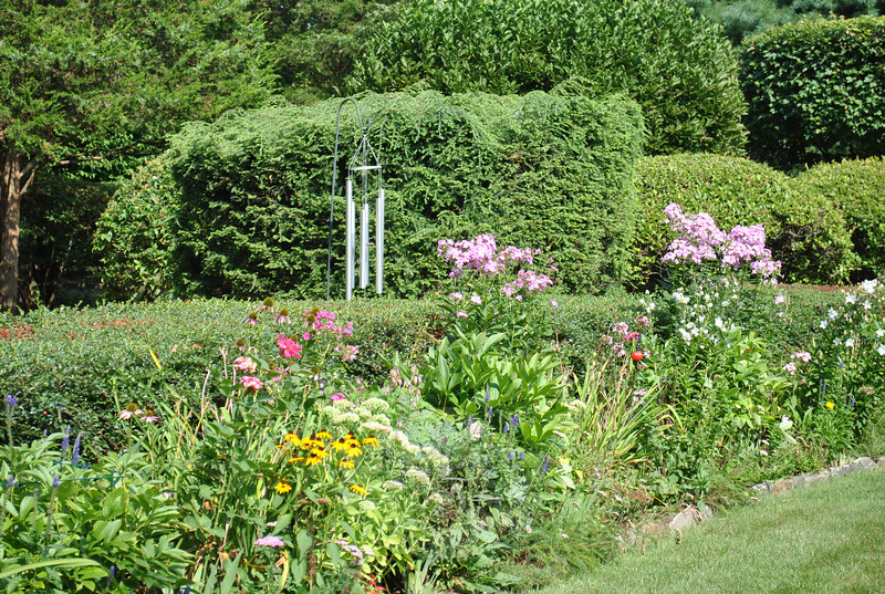 One of several border gardens planted by Marion Thompson is filled with her favorite perennials, such as black-eyed Susans, echinacea, phlox, lilies, yarrow, and Veronica, designed to bloom successively through the seasons.