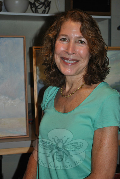 Joanne Conant, a recognized enamel artist and metalsmith, sits in her home studio, which she has expanded to include her newest venture, oil painting.