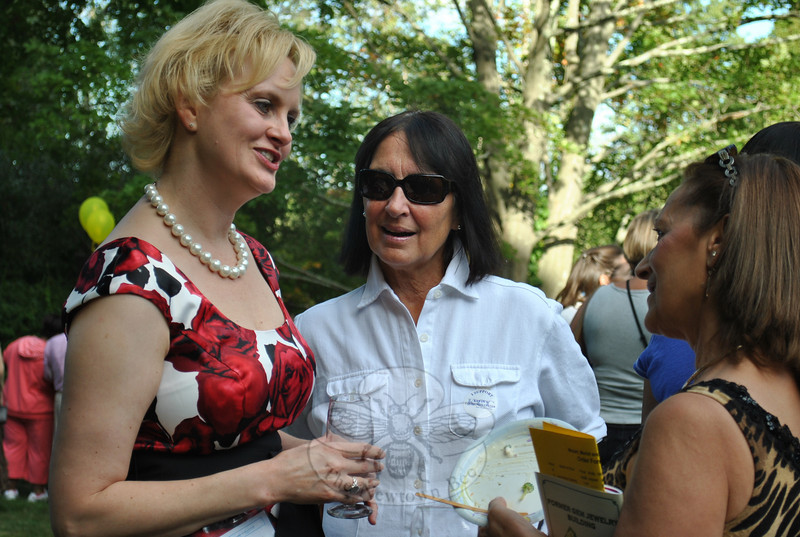 Kevin's Community Center Director Linda Pinckney, left, visits with Shane Miller, center, and Alice Correia, an RN volunteer at the clinic, during the September 11 Mozart, Merlot, and Mums fundraiser hosted by Ms Miller and her husband, George Miller, at their Main Street home in Newtown.  (Crevier photo)