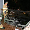 Sandy Hook Firefighters Ryan Lasher (left) and John Jeltema inspect the damage early on the morning of September 9, at a Yogananda Street home where an accidental fire damaged a section of a wooden rear deck and some outdoor furniture. The fire was reported by residents of an adjacent property. More than 20 Sandy Hook firefighters responded to the call.  (Hicks photo)