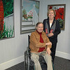 """Eclectica,"" an exhibition of paintings and bronze sculptures by the Newtown resident Anne Marie Foran opened Sunday, September 12, in the lower meeting room at C.H. Booth Library. Ms Foran is pictured with her husband and author, Ray Sipherd, among paintings and a decorative tri-fold screen she customized.  (Voket photo)"