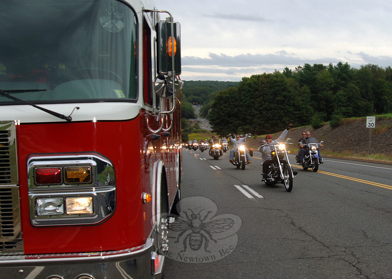 The Firehouse Motorcycle Ride on Sunday, September 12, raised funds for Newtown Hook & Ladder Fire Company #1. At one point riders passed a fire truck parked along Wasserman Way as they returned before noon Sunday to enjoy a pig roast.  (Bobowick photo)