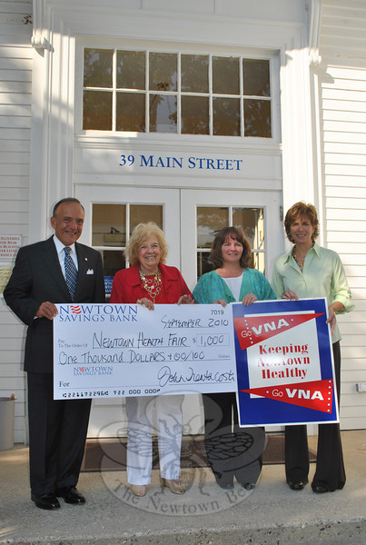 From left, John Trentacosta, president of Newtown Savings Bank, joins Mae Schmidle of the Newtown Visiting Nurse Association (VNA), Newtown Health Director Donna Culbert, and Dr Della Schmid, Tuesday, September 14, for a presentation of a check for $1,000 to support the September 25 Health Fair at Newtown Middle School. Newtown Savings Bank is the prime sponsor of the VNA-organized event.  (Crevier photo)