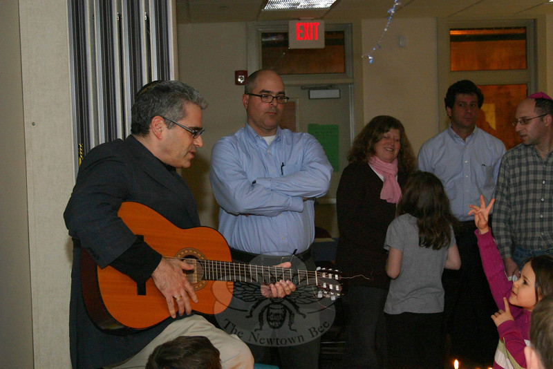 Rabbi Praver led thsoe who gathered for the Community Candle Lighting & Potluck Dinner at Congregation Adath Israel in a sing-along before dinner on December 7.  (Hicks photo)
