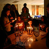 Congregation Adath Israel celebrated the seventh night of Hanukkah with a Community Candle Lighting & Potluck Dinner Tuesday, December 7. Families brought their menorahs to the synagogue, where they were gathered onto one table while Rabbi Shaul Praver led the group in song. Hannah Fink, on the left, had the honor of lighting her family's Hanukiah. While doing so, she held the attention of Charlotte Praver, while brother Shane Praver was equally enthralled with the lighting of another nearby menorah. Dinner was then followed with a performance by the recently formed Adath Israel Choir.  (Hicks photo)