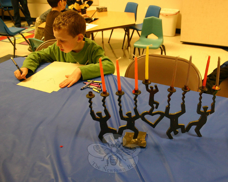 Ethan Fink passed some of the time before the beginning of Congregation Adath Israel's Community Candle Lighting & Potluck Dinner on December 7 by drawing. His family's menorah, or Hanukiah, is at right.  (Hicks photo)