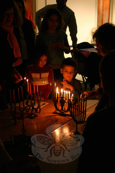 Charlotte and Shane Praver were enthralled while a member of Congregation Adath Israel lit a menorah in front of them during a Community Candle Lighting & Potluck Dinner on December 7.  (Hicks photo)
