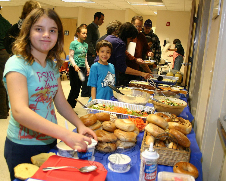 Emily Wiener was all over the bagels and cream cheese when it was time to begin dinner on December 7. She and her family attended the Community Candle Lighting & Potluck Dinner at Congregation Adath Israel that evening.  (Hicks photo)
