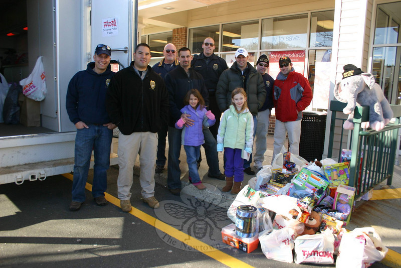 Members of Newtown Police Union who collected donations for Toys For Tots last weekend included, from left, Sergeant Dave Kullgren, Officer Richard Monckton, Officer Robert Haas, Officer Matthew Wood (with his daughters), Officer Rich Chapman, Detective Daniel McAnaspie, and Officer Scott Ruszczyk. On the right is Bruno Carmo from the recently opened Meat House, who offered gift certificates to the first 100 donors on December 4.  (Hicks photo)