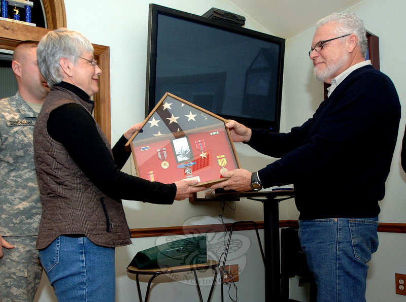 Joan Bowles recently received medals on behalf of her late brother George Bresson. The shadowbox of medals reflects his time in Vietnam from 1966 to 1967. With her is Carl Besson, who was her brother's bunkmate and a fellow veteran. The two joined Newtown VFW Post 308 members on December 5 to honor her brother, who had died in 1988 but only recently received the Bronze Star Medal for valor that the Army had awarded to him following the Battle of Suoi Tre.  (Bobowick photo)
