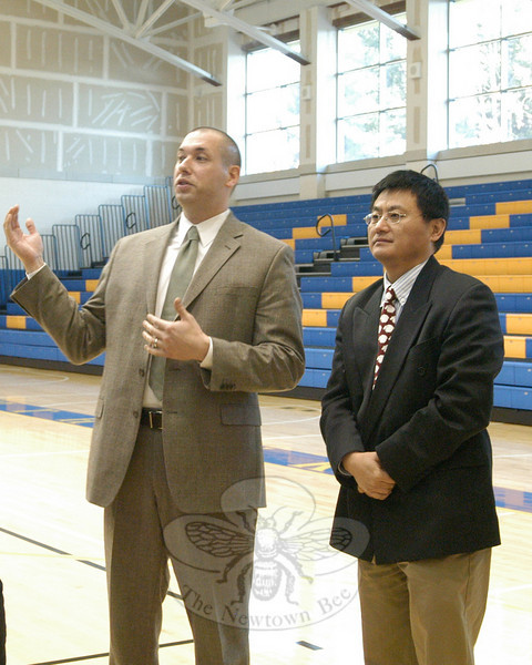 Newtown High School Assistant Principal Jason Hiruo, left, spoke to visiting Chinese Ministry of Education delegates in the school's gymnasium. To Mr Hiruo's right, Ministry of Education Deputy Director General Jidong Zhang listens before translating for the group.  (Hallabeck photo)
