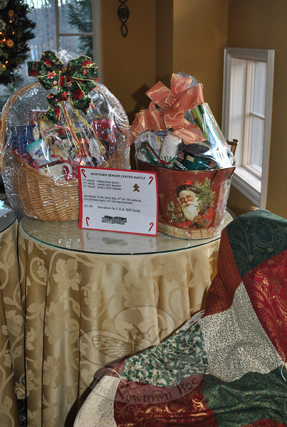 It was hard for most guests to pass by the table where gift baskets, a quilt and other raffle tickets were being sold.  (Crevier photo)