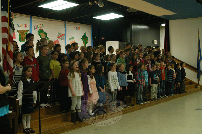 "Head O' Meadow second grade students performed first for the whole school then for parents on Tuesday, November 30. Students shared an adaptation of, ""How to Make an Apple Pie and See the World,"" written by Marjorie Priceman, by singing songs from around the world and dancing. Principal Barbara Gasparine and Newtown Public Schools Director of Music Michelle Hiscavitch both said the performance exemplified integrating reading and writing into other areas of the curriculum. ""They sang it a cappella,"" said Ms Hiscavitch. ""That's quite an accomplishment for second grade.""  (Hallabeck photo)"