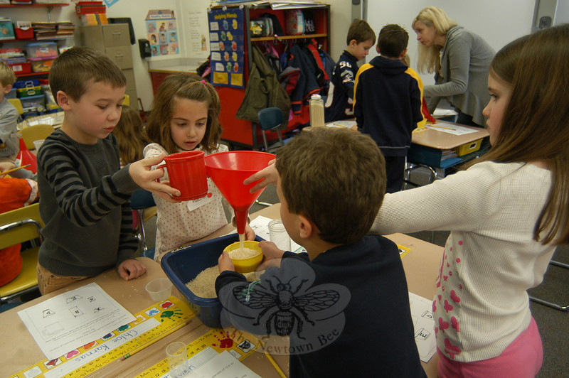 Head O' Meadow students -- clockwise from left, Smith Arend, Rachel Arena, Victoria Gioiele and Ryan Bicho -- measured how many cups of rice filled a pitcher during the school's 13th Annual Measurement Morning, held on Friday, December 10.  (Hallabeck photo)