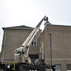 The 127-foot arm of the Quick Pick crane lifted Stuart Hall of Brook Farm Metal Works and his assistant Amilcar Garcia up to the top of Hawley School on Friday, December 10, to replace the newly refurbished weathervane that Mr Hall repaired over the course of several weeks.  (Crevier photo)