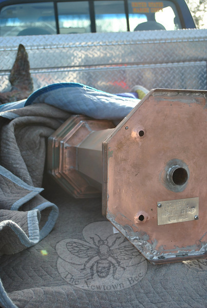 The flute and weathervane lie wrapped in protective cloth in the back of Stuart Hall's truck, while Mr Hall and Mr Garcia did preliminary carpentry on the cupola, and placed the pedestal.  (Crevier photo)