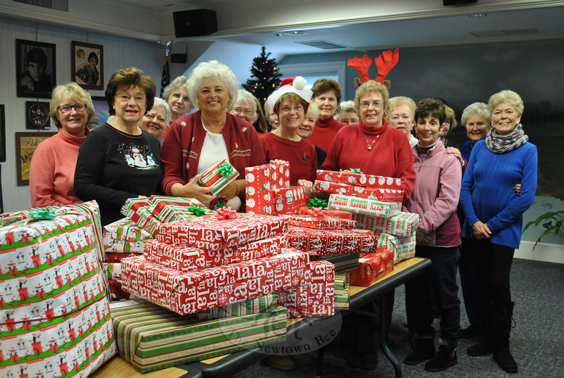 Vice president JoAnn Bruno, front row, second from left, joined Newtown Woman's Club, GFWC, Inc, Newtown Fund donation co-chairpersons Pat McCarthy, center left, and Marge Cassin, center right (wearing antlers), and several other members of the club on Tuesday morning, December 14, behind a table piled high with gifts wrapped for local families adopted by the Woman's Club this holiday season. The Newtown Woman's Club takes part in the Newtown Fund holiday family adoption event every year. A group of members from Newtown Woman's Club also went to Rocky Hill Veteran's Hospital on Monday, December 13, to wrap gifts for the veterans.  (Crevier photo)