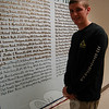 Newtown High School junior Sean Decker stands with a mural that lists the names of Connecticut soldiers killed in action that he created for the school's Junior/Senior Project course. (Hallabeck photo)