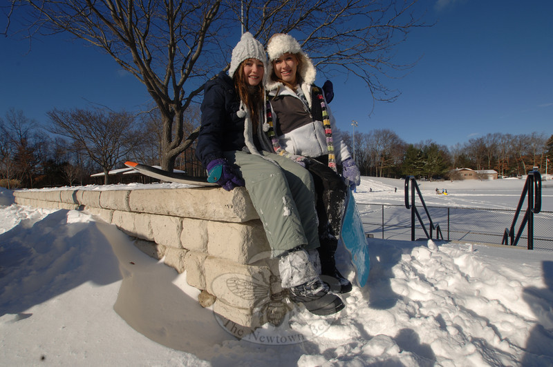 Annie Hoffman, left, and Lindsay Skalkos kept warm in their snow caps and mittens Monday, where they watched a revolving troupe of sledders move up and down the hillside.  (Bobowick photo)