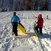Packing the snow into slick tracks, sledders who had rushed down the slick slope at Treadwell Park Monday soon trudged back up the incline for another run.  (Bobowick photo)