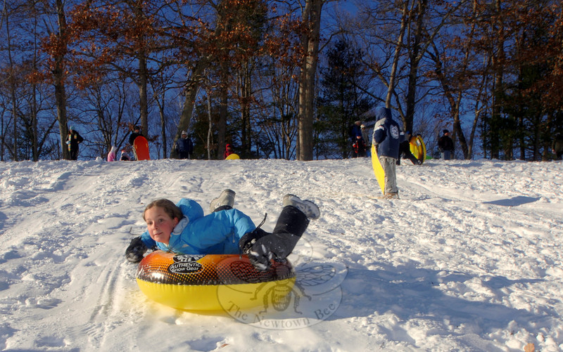 Zoe Beals rushed down the snowy slope on her inflated tube Monday, December 27, at Treadwell Park.  (Bobowick photo)