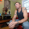 Jason Conley relaxes at home, comfortable in his tattoos. Nearby is a folder filled with sketches of designs he will use in future body art.  (Bobowick photo)