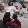 Veronica London from High Tough High Tech of Connecticut, a company that provides science programs for students, was busy in Hawley Elementary School's science lab on Thursday, December 16, giving presentations to second grade students. Kristin Compton's class, above, learned how mass means objects have space, and that space cannot take up another object's space. To demonstrate this, Ms London had a clear bottle filled halfway with vinegar. Baking soda from a blue balloon attached to the bottle's opening was dropped into the liquid, to reveal the balloon being expanded because the baking soda could not take up the vinegar's space. After viewing the experiment, students went on to perform their own hands-on experiments. (Hallabeck photo)