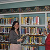 C.H. Booth Library staff member Molly Nostrand, left, and librarian Judy Craven place books on the shelves in the Large Print Room. A top layer of shelving has been crafted and installed by Newtown woodworker Paul Morin, allowing the library to add new books to the popular large print collection.  (Crevier photo)