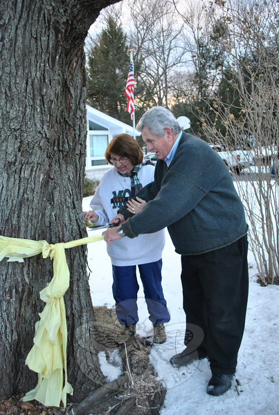 """Lorraine and Michael Hurley happily cut down the yellow ribbon that has been tied around the tree in ront of their South Main Street home for the past year. The ribbon was tied to the tree in December 2009 when their son-in-law, US Army Major Ben Wallen, was sent to Iraq. """"He returned to us safely this past December, with a surprise,"""" said Mrs Hurley. """"He was awarded the Bronze Medal, the Army's third highest honor."""" The yellow ribbon snipped from the tree, Wednesday, January 5, is the second time the Hurleys have made short work of a band of yellow. Four years ago, Mr and Mrs Hurley dispensed with the ribbon they had tied up to honor their daughter, Michaela Hurley, upon her safe return from Afghanistan. """"We are so excited and happy to have Ben back stateside,"""" Mrs Hurley said. """"I hope I don't have to put anymore yellow ribbons up now."""" In the background is an American flag presented by Maj Wallen to his in-laws.  (Crevier photo)"""