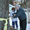 "Lorraine and Michael Hurley happily cut down the yellow ribbon that has been tied around the tree in ront of their South Main Street home for the past year. The ribbon was tied to the tree in December 2009 when their son-in-law, US Army Major Ben Wallen, was sent to Iraq. ""He returned to us safely this past December, with a surprise,"" said Mrs Hurley. ""He was awarded the Bronze Medal, the Army's third highest honor."" The yellow ribbon snipped from the tree, Wednesday, January 5, is the second time the Hurleys have made short work of a band of yellow. Four years ago, Mr and Mrs Hurley dispensed with the ribbon they had tied up to honor their daughter, Michaela Hurley, upon her safe return from Afghanistan. ""We are so excited and happy to have Ben back stateside,"" Mrs Hurley said. ""I hope I don't have to put anymore yellow ribbons up now."" In the background is an American flag presented by Maj Wallen to his in-laws.  (Crevier photo)"