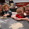 Newtown High School student Sam Phillips, left, and Rachel Wiberg, right, helped Nurtury preschool students bake sugar cookies in one of the school's culinary rooms on Monday, December 20.  (Hallabeck photo)