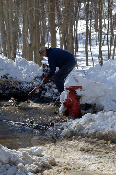 Among the many people working diligently to clear the two-plus feet of snow that buried items, including this fire hydrant on West Street, were town Public Works Department crews. Milt Adams tried to direct the water's flow as it gushed into the street Thursday. A plow accidentally clipped the hydrant while clearing snow.  (Bobowick photo)