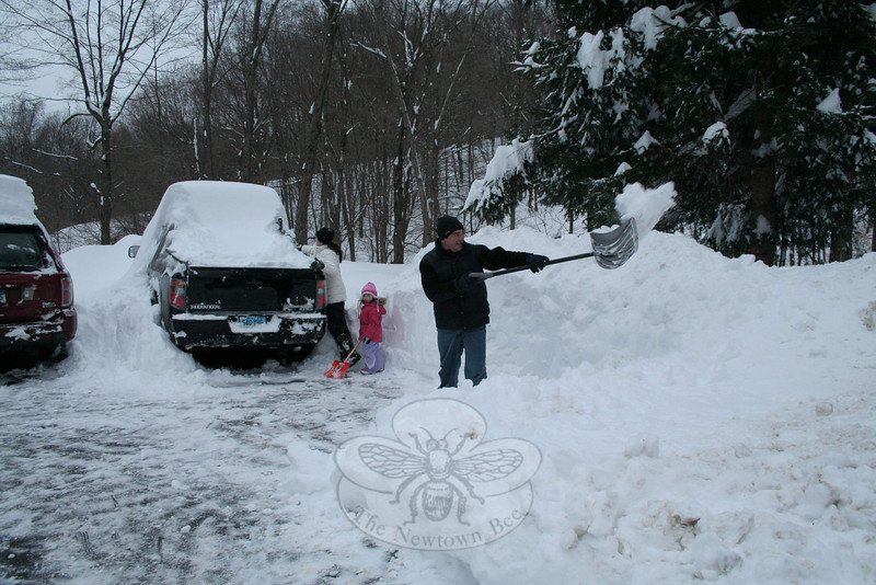 It took three hours for the Montoya family — from left, Lina, Isabelle, and John — to clear about three-quarters of their approximately 1,000-square-foot driveway and a short sidewalk from the driveway to their house Wednesday afternoon.  (Hicks photo)
