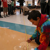 Lincoln Gray measured to see if the team hit the midway point with Odyssey of the Mind judge Bob Zinser, on Friday, January 14. Lincoln and his teammates on Team 6 had worked together to find the midway point for a number of strings in Reed's cafetorium during this year's Spontaneous Scrimmage.  (Hallabeck photo)