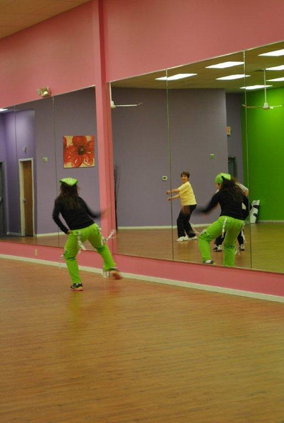 Instructor Laura Levy and Z Place member Elaine Stanton, of Newtown, are reflected in the room-length mirror at the new fitness studio. Watching the instructor keeps your mind as active as the body during Zumba classes, says Ms Stanton.  (Crevier photo)