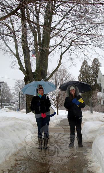 With light rain dripping from their blue umbrellas, friends Katie Pessin, left, and Taylor Truchsess were the only spots of color along Main Street's slick sidewalks lined with melting snow.  (Bobowick photo)