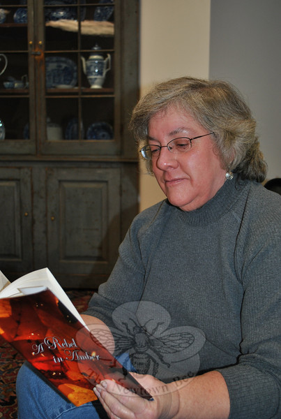 Sandy Hook author Debra Thrall looks over a copy of her novel, A Rebel in Amber, published in November 2010 by Xlibris.  (Crevier photo)