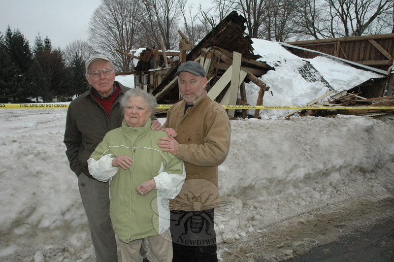 The Fadus family, from left, Charlie, Jean, and their son Paul, stand in front of the family property at 57 West Street on Wednesday morning, where an antique barn had collapsed under the weight of recent accumulated snow. Hook & Ladder firefighters responded to secure the area.  (Gorosko photo)