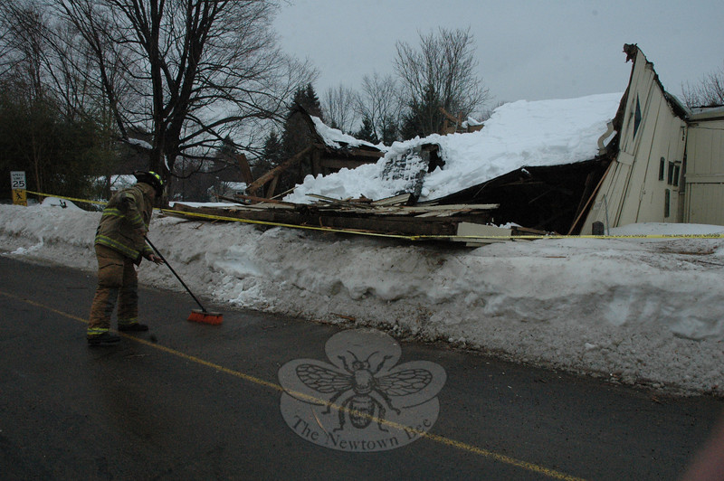 A Newtown Hook & Ladder firefighter sweeps some debris off the pavement near 57 West Street on Wednesday morning, where an antique barn collapsed under the weight of accumulated snow.  (Gorosko photo)