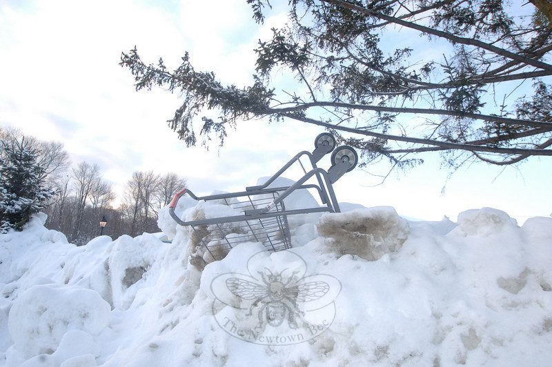A shopping cart caught by a plow sat high overhead in the rising heaps of snow plowed off of the Big Y shopping plaza's lots.  (Bobowick photo)