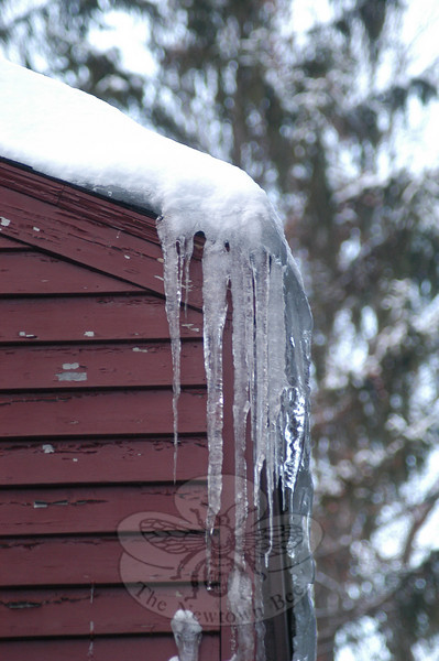 Too much snow and ice, and unusually cold weather, has resulted in ice dams like this forming at the edge of roofs all over Newtown. In some cases, the result has been water pouring down interior walls, or leaking stealthily between the exterior and interior walls. Removing the snow from rooftops, and ice out of gutters, is essential to avoid damage, say area experts.  (Clark photo)