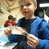 Head O' Meadow first grader Alex Lensges holds up his nearly completed two copper leaves that will be added to a schoolwide art project installation. Each leaf will have the creator's initials on it.  (Hallabeck photo)