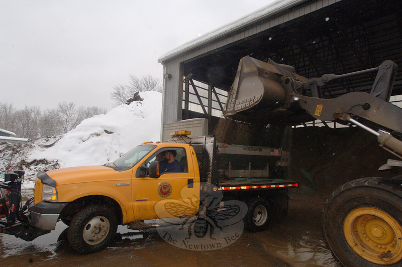 Crew Chief Anthony Capozziello parks a town truck beneath a loader pouring a fresh supply of salt and sand into the back. He is among Public Works town crew members who work through snow storms to clear and sand Newtown streets.  (Bobowick photo)