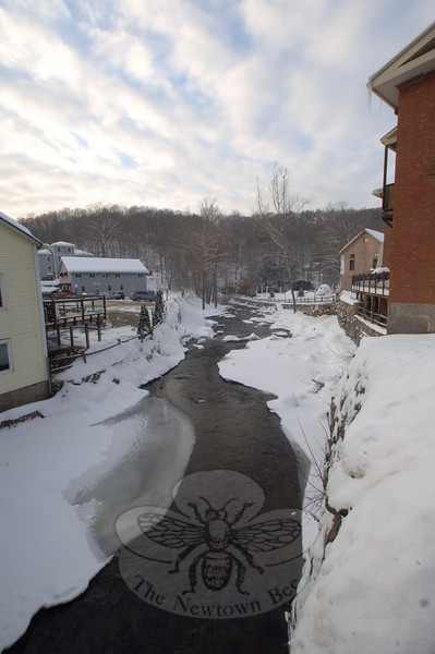 The Pootatuck River running through Sandy Hook Center cuts a corridor through the accumulating snow piling up this season.  (Bobowick photo)