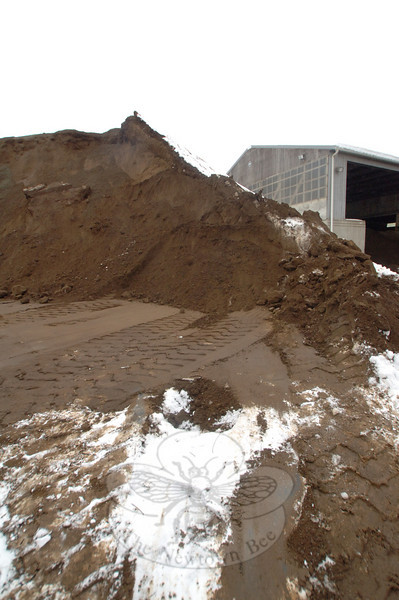 The Public Works garage stands beside shrinking sand piles as the crews continue this month to use the supply on roads repeatedly covered by snow.  (Bobowick photo)
