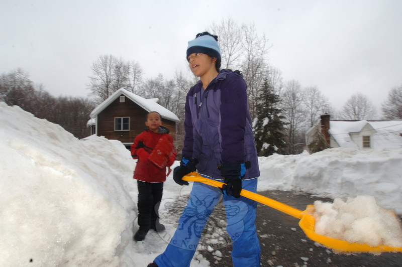 Jazmyn Edmond moves a shovelful of snow off her driveway in Sandy Hook Wednesday morning with the help of her brother Calum, in the background.  (Bobowick photo)