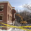 A backhoe creeps over piled debris to pull apart the remaining wing of Litchfield House.  (Bobowick photo)