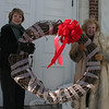 In conjunction with the observation of National Health Month by the American Heart Association and related activities and suggestions issued by Newtown Parks & Recreation Department and the Newtown Health District, the Newtown chapter of Visiting Nurse Association has hung its large grapevine wreath at Edmond Town Hall for February. VNA members Joan Reynolds, left, and Mae Schmidle prepared the wreath with ribbon and a new red bow for placement in the cupola at 45 Main Street on January 24.  (Hicks photo)